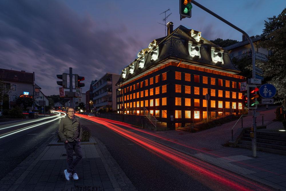 Die Skulptur mit flizenden Lichter der Autos und Andreas Sarow an der Straße