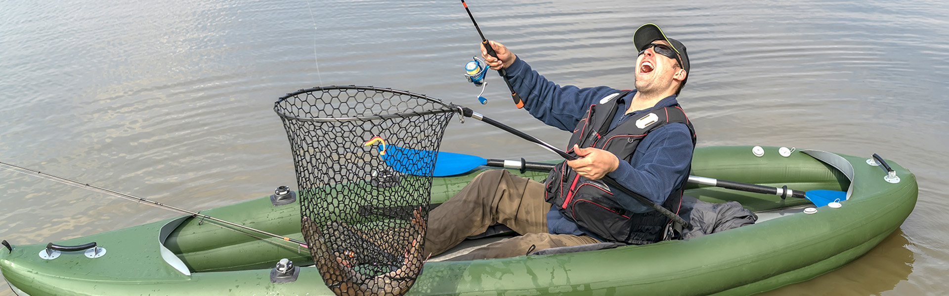 Kayak fishing. Fisherman catch pike fish on inflatable boat with fishing tackle at lake.